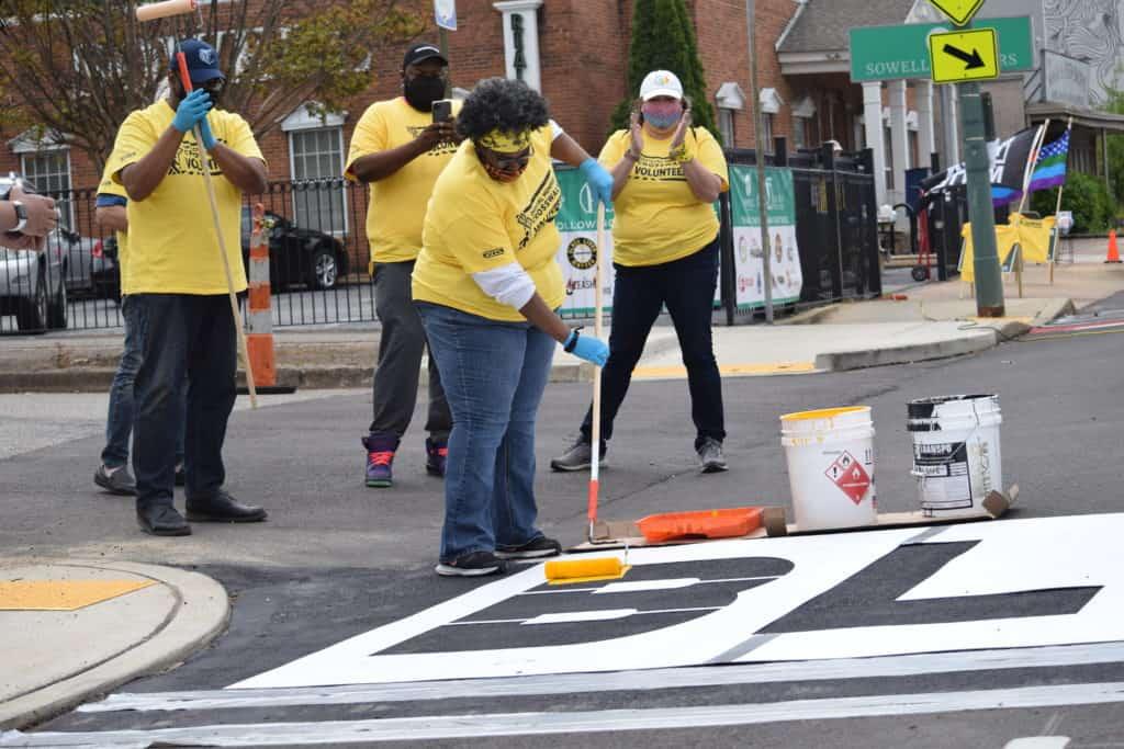 Daphne Butler, who designed the crosswalks, painted the B in Black Lives Matter.